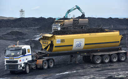 FILE - Heavy equipment is seen loading coal onto a truck at PT Adaro Indonesia coal mining in Tabalong, Kalimantan island, Indonesia Oct. 17, 2017.