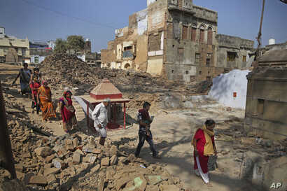 Hindu devotees walk barefoot through debris of demolished houses to reach river Ganges at the site of a proposed grand promenade, March 19, 2019. The $115 million promenade is one of a number of India Prime Minister Narendra Modi's religious glamour...