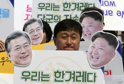 "An activist with cutouts of South Korean President Moon Jae-in, left, and North Korean leader Kim Jong Un participates  in a rally welcoming the planned summit between South and North Korea in Seoul, South Korea, April 25, 2018. The signs read: "" We ..."