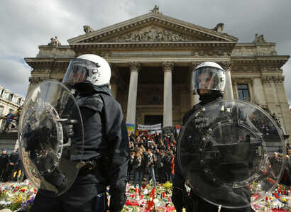 Police in riot gear protect one of the memorials to the victims of the recent Brussels attacks, as right wing demonstrators protest near the Place de la Bourse in Brussels, Sunday, March, 27, 2016.