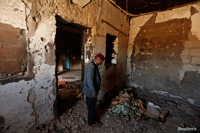 FILE - Hamid Ishi stands in his house, which was taken over by Islamic State jihadists and damaged during fighting with government forces, in Ben Guerdane, Tunisia, April 10, 2016.