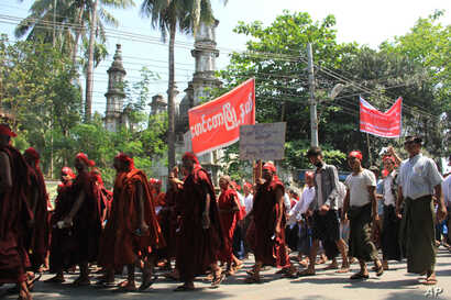 Hard-line Buddhists walk by a mosque during a protest march, led by Rakhine State's dominant Arakan National Party, against the government's plan to give citizenship to some persecuted Rohingya Muslims, March 19, 2017.