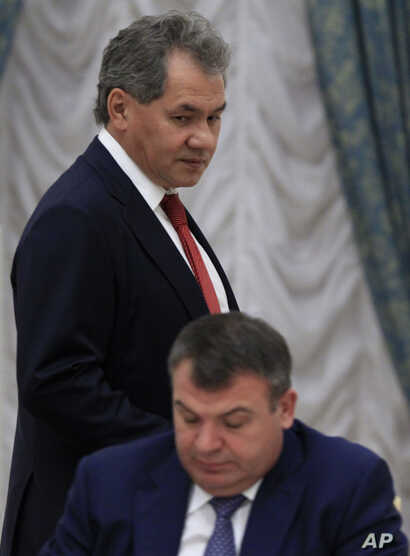 Governor of Moscow Region Sergei Shoigu passes by then Defense Minister Anatoly Serdyukov before a session of the State Council's Presidium at the Kremlin in Moscow, October 9, 2012.