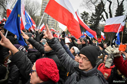 Demonstrators display Polish and European Union flags during the third day of a protest outside the Parliament building in Warsaw, Dec. 18, 2016.
