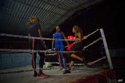 Olympic silver medalist Emilio Correa Jr., center, instructs Idamelys Moreno, right, and Legnis Cala, at a sports center in Havana, Cuba, Jan. 24, 2017.
