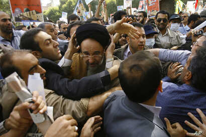 Escorted by his bodyguards, reformist former Iranian President Mohammad Khatami, center, is attacked by hard-liners as he attends a Quds Day rally, in Tehran, Sept. 18, 2009.