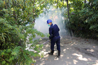 A worker fumigates an area in Yangon, Myanmar, in an attempt to destroy mosquitoes that might carry the Zika virus, Nov.18, 2016.