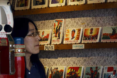A woman walks past a rack displaying the cards depicting former Chinese leader Mao Zedong and the great army of the Cultural Revolution for sale at a souvenir shop in Beijing, May 17, 2016.