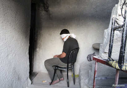 FILE - A blindfolded man waits to be interrogated in a prison in Aleppo, Syria, Oct. 6, 2014. Activists say more than 110,000 detainees are currently being held in Syria, most of them by the government of President Bashar al-Assad.