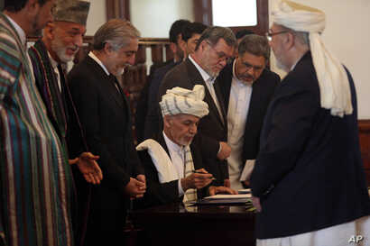 Afghan President Ashraf Ghani, center, signs a peace agreement with Gulbuddin Hekmatyar, a notorious warlord on terrorist blacklists, at the presidential palace in Kabul, Sept. 29, 2016.