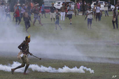 An indigenous man runs amid tear gas fired by police during a protest for the demarcation of indigenous lands outside the National Congress in Brasilia, Brazil, April 25, 2017.
