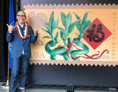 Kam Mak stands next to an image of the Year of the Dog stamp he created, which was dedicated in Honolulu. Mak is giving the friendly Hawaiian shaka sign, which means hang loose.