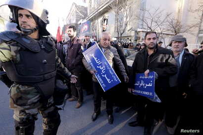 An Iranian riot policeman stands guard as protesters hold street signs with the name of Shi'ite cleric Sheikh Nimr al-Nimr during a demonstration condemning his execution in Saudi Arabia, outside the Saudi Arabian Embassy, in Tehran, January, 3, 2016...