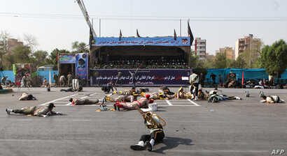 This picture taken on September 22, 2018 in the southwestern Iranian city of Ahvaz shows injured soldiers lying on the ground at the scene of an attack on a military parade that was marking the anniversary of the outbreak of its devastating 1980-1988...