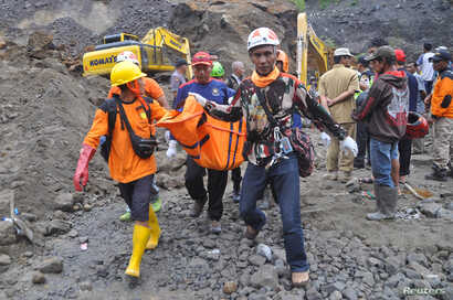FILE - Rescue team members carry the body of a miner after a landslide hit Srumbung Village in Magelang, Indonesia, Dec. 18, 2017.
