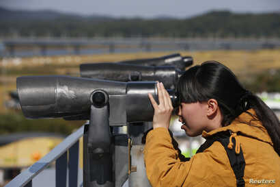 FILE - A Chinese tourist looks towards the north through a pair of binoculars at the Imjingak pavilion near the demilitarized zone which separates the two Koreas, in Paju, north of Seoul, Oct. 16, 2013.