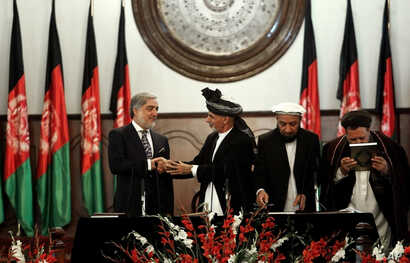 Afghan President Ashraf Ghani Ahmadzai, second left, shakes hands with chief executive Abdullah Abdullah, left, during his inauguration ceremony at the presidential palace in Kabul, Afghanistan, Monday, Sept. 29, 2014. Ghani Ahmadzai replaces Hamid K...