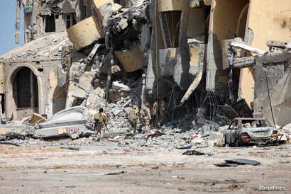 Libyan forces allied with the U.N.-backed government walk through a destroyed building during a battle with Islamic State militants in Sirte, Libya, Oct. 2, 2016.
