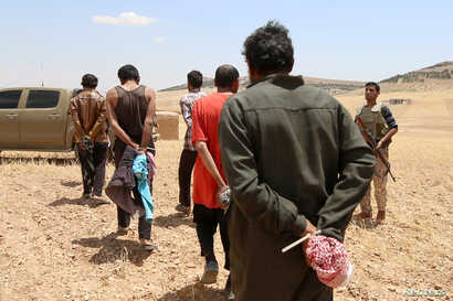 Men, who the Democratic Forces of Syria fighters claimed were Islamic State fighters, walk as they are taken prisoners after SDF advanced in the southern rural area of Manbij, in Aleppo Governorate, Syria, May 31, 2016.