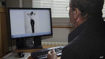 Slovenian retired fashion photographer Stane Jerko looks at a photo of Melanija Knavs, now known as Melania Trump, from their first photo session, in Ljubljana, Slovenia, in this photo taken from AP video Feb. 11, 2016.