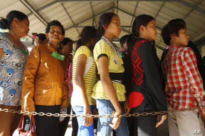 FILE - Cambodian villagers line up to enter a courtroom before the first appeal hearings against two former Khmer Rouge senior leaders, Khieu Samphan and Nuon Chea, at the U.N.-backed war crimes tribunal in Phnom Penh, Cambodia, July 2, 2015.