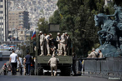 FILE - Russian soldiers stand on a truck in central Damascus, Syria, Sept. 14, 2018.