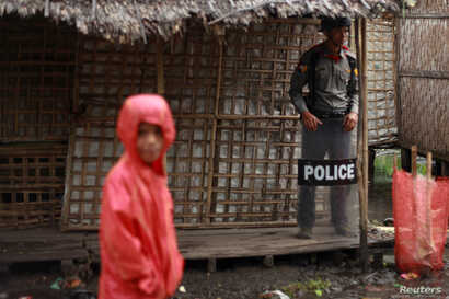 FILE - A policeman stands guard as former U.N. chief Kofi Annan (not in picture) attends a meeting with local leaders at the Aung Mingalar Rohingya internally displaced persons (IDP) camp in Sittwe, Myanmar, Sept. 7, 2016.