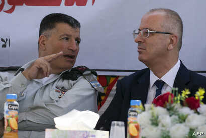 FILE - Palestinian prime minister Rami Hamdallah, right, sits next to Major General Yoav Mordechai, head of COGAT, the Israeli defense ministry agency responsible for civilian affairs in the Palestinian territories, as they attend a ceremony in Jalam...