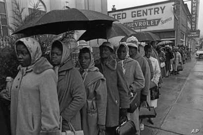 It rained all day but that did not dampen the spirits of blacks determined to register to vote. They stood in the rain trying to register in a priority book to take voter registration test in Selma, Alabama, Feb. 17, 1965.