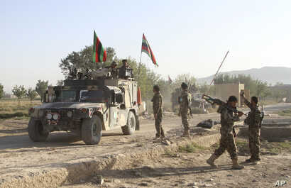 FILE - Afghan national army soldiers stand near the body of a Taliban fighter killed in Ghazni province, eastern Afghanistan, Sept. 14, 2015.