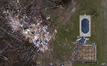 Debris from a home litters a yard the day after a tornado blew it off its foundation, lower right, in Beauregard, Alabama, March 4, 2019.