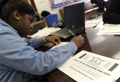 FILE - Akira Lee, a senior at Roosevelt High School, fills out a college enrollment application at her school in Washington.