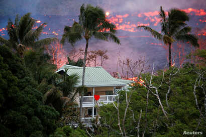 Lava flows near a house on the outskirts of Pahoa during eruptions of the Kilauea volcano in Hawaii, May 19, 2018.