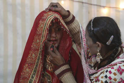 FILE - A woman helps a Pakistani Hindu bride prepare for her wedding in Karachi, Pakistan.
