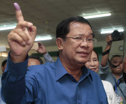 FILE - Cambodian Prime Minister Hun Sen shows off his inked finger after voting in local elections at Takhmau polling station in Kandal province, southeast of Phnom Penh, Cambodia, June 4, 2017.