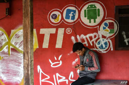 FILE - A man plays with his mobile phone in front of a cellular provider's advertisement with a Facebook logo in Jakarta, March 22, 2018.