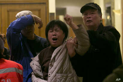 A relative of one of the Chinese passengers aboard flight MH370 grieves after being told of the latest news in Beijing, March 24, 2014.