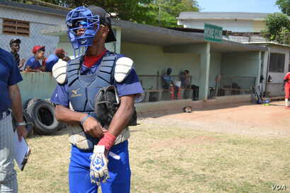 José Hernán, a catcher representing one of Havana's three municipality teams, prepares to play at the 50th Anniversary Stadium in Cuba. He says baseball is to Cuba as football is to Brazil.