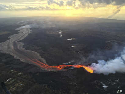 In this July 17, 2018 photo provided by the U.S. Geological Survey, sunrise is seen over the Kilauea volcano lower East Rift Zone in Hawaii.