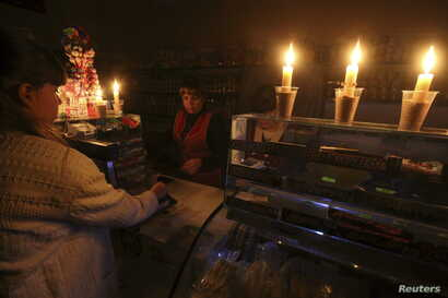 A customer visits a grocery lit with candles Nov. 22, 2015, due to a power cut, in Simferopol, Crimea.