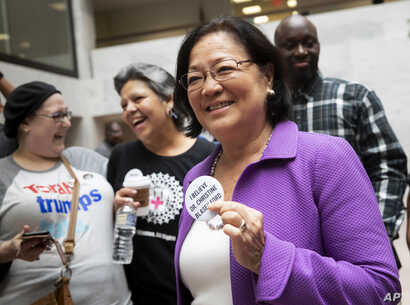 Sen. Mazie Hirono, D-Hawaii, a member of the Senate Judiciary Committee, is welcomed by protesters opposed to President Donald Trump's Supreme Court nominee, Brett Kavanaugh, as they demonstrate in the Hart Senate Office Building on Capitol Hill in W...