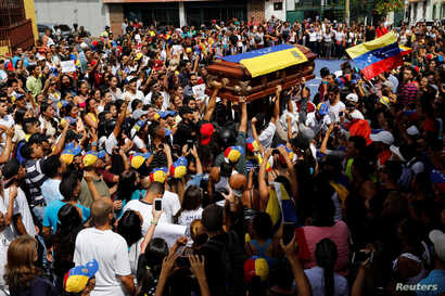 Mourners carry the coffin of Neomar Lander, who died during a protest against Venezuelan President Nicolas Maduro's government, during his funeral in Guarenas, Venezuela, June 9, 2017.