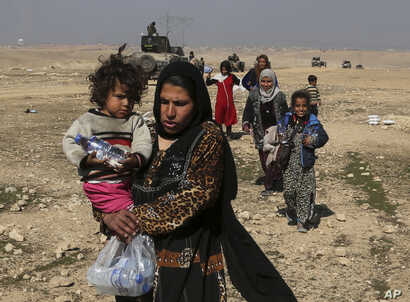 Displaced Iraqis flee their homes due to fighting between Iraqi special forces and Islamic State militants, on the western side of Mosul, Iraq, Feb. 2017.