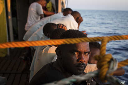 migrants rest on the deck of the Open Arms boat, after being rescued off the coast of Libya in the early hours of the nigh of Thursday, Aug. 2, 2018.