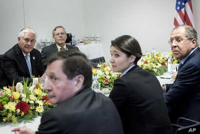 U.S. Secretary of State Rex Tillerson, left, Russia's Foreign Minister Sergei Lavrov, right, and others wait for the start of a meeting at the World Conference Center, in Bonn, Germany, Feb. 16, 2017, as part of a broader G-20 meeting.