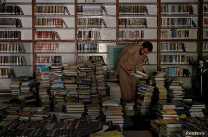 A librarian selects books that are being cataloged in the library at the Al-Nadwa Madrassa in Murree, Pakistan, Oct. 24, 2017.