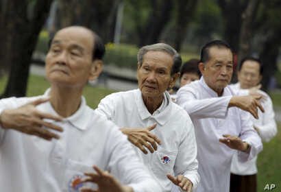 FILE - Men exercise at a park in Bangkok, Thailand, Dec. 16, 2011.