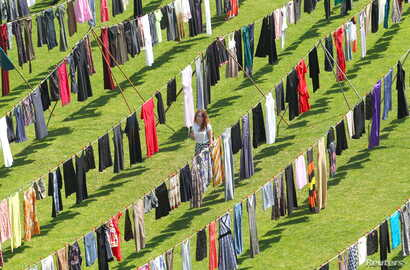 "A woman walks among dresses and skirts hanging inside a stadium, in an art exhibition titled ""Thinking of You"" by Kosovo-born, London-based artist Alketa Xhafa-Mripa, in Pristina, June 12, 2015. Dresses and skirts donated by Cherie Blair and Rita Ora..."