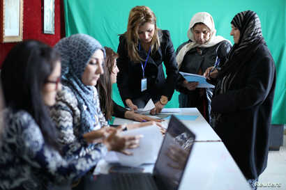 People register their names before voting at a polling station in Qamishli, Syria, Dec. 1, 2017.
