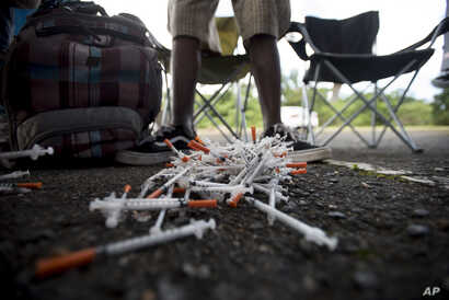 FILE - A drug user turns in his used syringes to volunteers from the Intercambios Puerto Rico needle exchange program, in order to get new, clean ones, in an area popular with drug users in Humacao, Puerto Rico, Dec. 14, 2018.